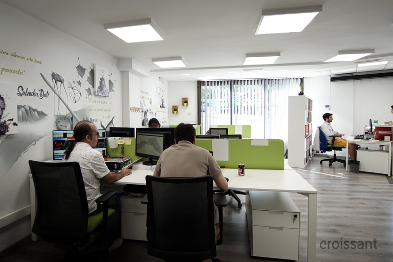 a room with people sitting at a desk