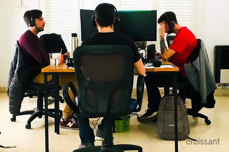 a group of people sitting at a desk in an office chair