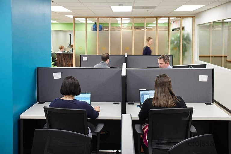 a group of people sitting at a desk in a room