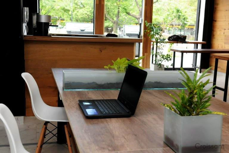 a laptop computer sitting on top of a table next to a window
