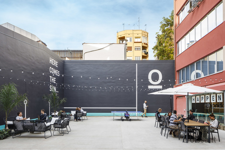 a group of people sitting at a table in front of a building