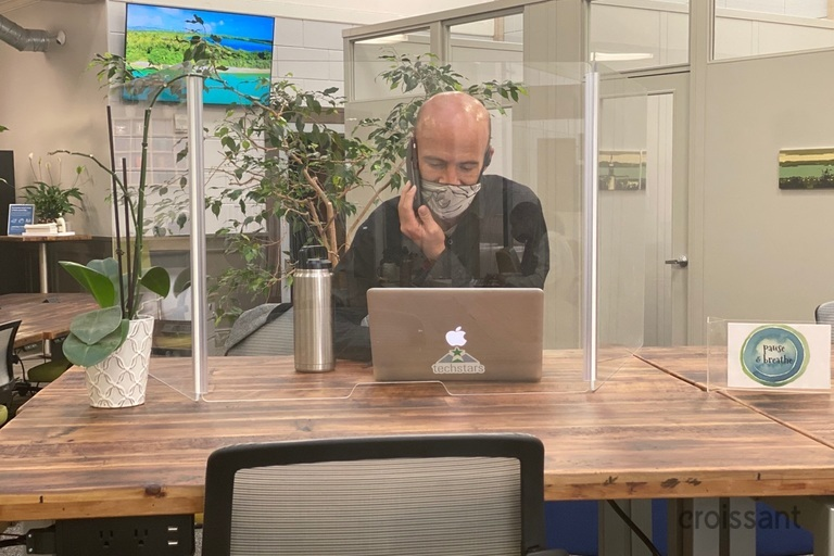 a man sitting at a table using a laptop