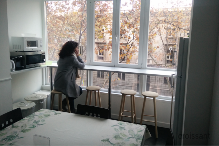 a person sitting at a table in front of a window