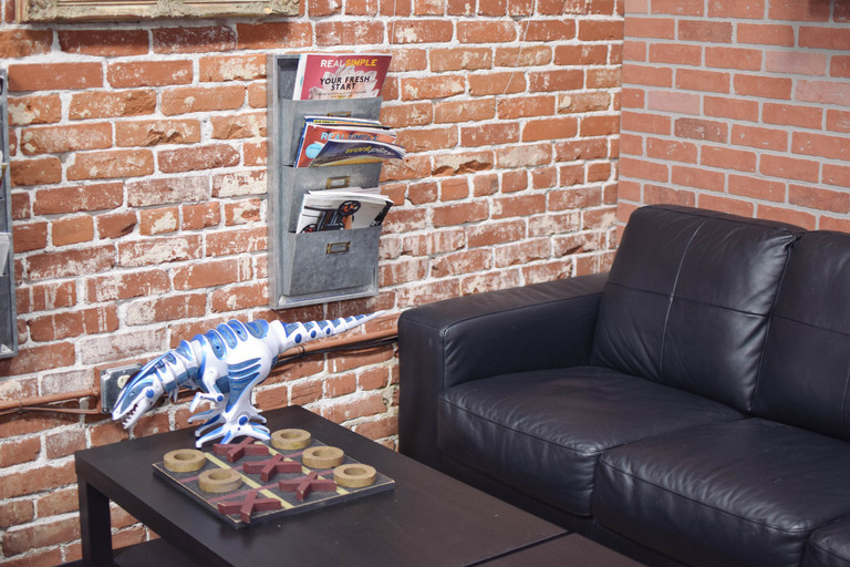 a brown leather couch in a living room with a brick wall