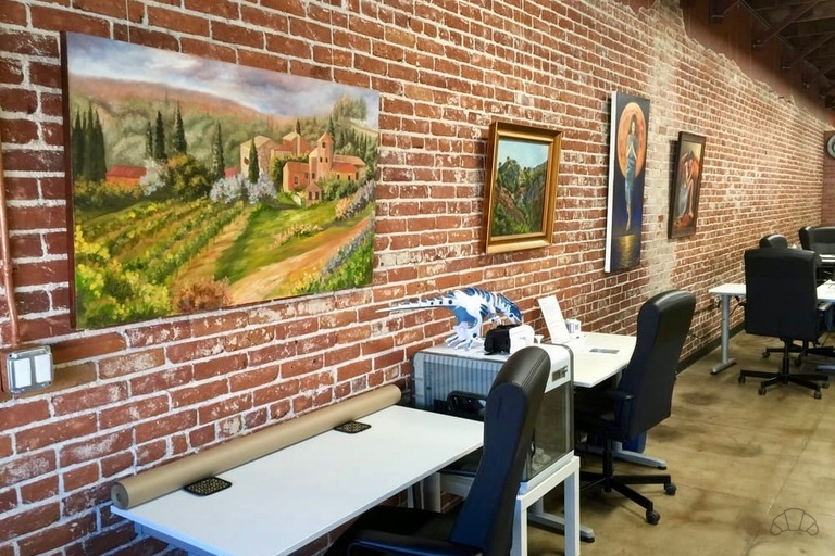 Beautiful artwork on exposed bricks throughout the coworking space with ergonomic chairs