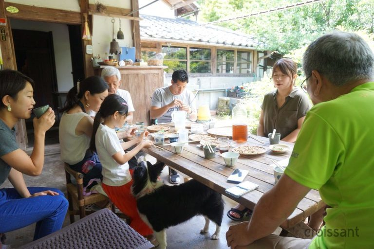 a group of people sitting at a table with a dog